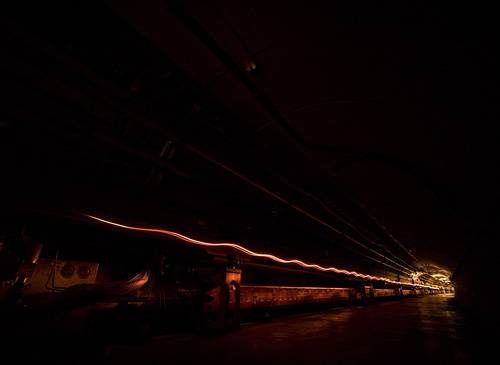 An artistic image depicts the acceleration of particle beams in the Tevatron tunnel