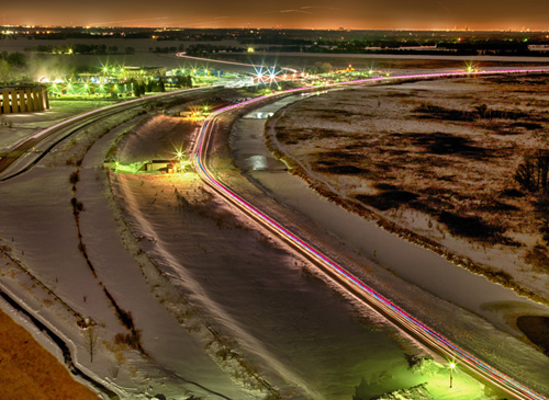 Vehicles with lights circle the Tevatron ring at night