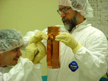 Project manager Dan Bauer from Fermilab holds one tower of detectors as Vuk Mandic from UC Berkeley examines them. Each tower of detectors contains 1 kilogram of germanium for detecting dark matter and 200 grams of silicon to distinguish WIMPs from neutrons. Thin layers of silicon, aluminum, and tungsten covering the detector surfaces measure both the heat and charge released when a particle interacts inside.