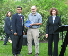 Bharat Mathur (left) and Elizabeth McCance (right) presented the award to Rod Walton (center).