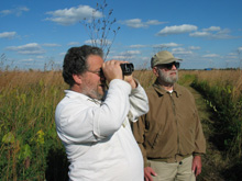 Joel Greenberg (left) explores Fermilab's prairie with Bob Betz.