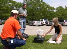 Christie Brayer shows a mosquito trap to Mike Becker and Mark Schiltz